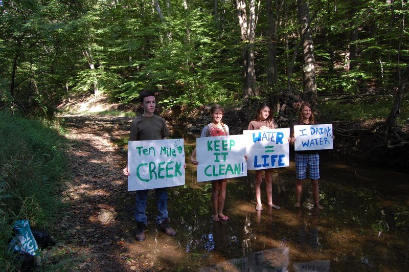 PoolesvilleH.S.Global Ecology Students holding signs at Ten Mile Crk photog_DMC